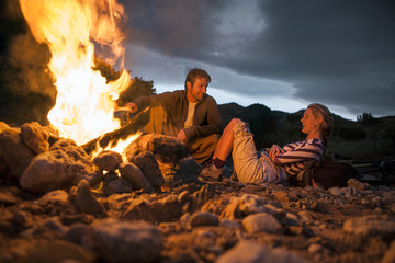 Young couple relaxing and laughing beside glowing campfire.