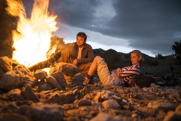 Content young couple sitting by a glowing campfire.