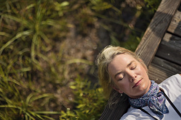 Woman lying down and resting on wooden forest walkway.