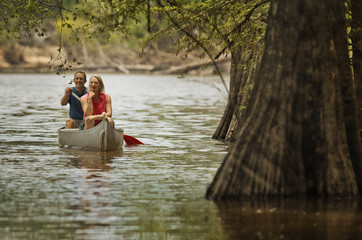 Smiling mature couple canoeing on a river in the woods.
