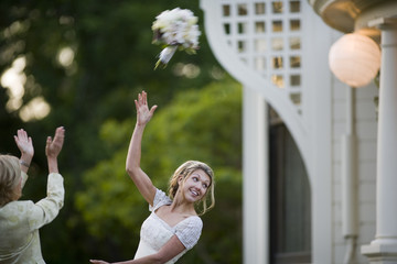 Young adult woman throwing a bouquet on her wedding day.