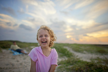 Smiling young girl on a beach at sunset.