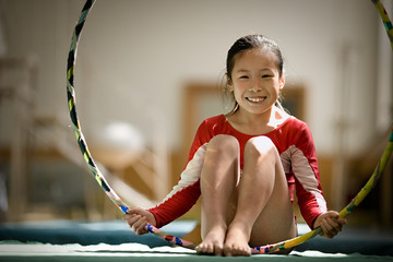 Portrait of a girl playing around with a hula hoop in a gym.