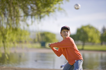 Boy swinging softball bat in park