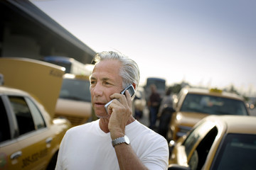 Mature man talking on his cell phone in a car park.