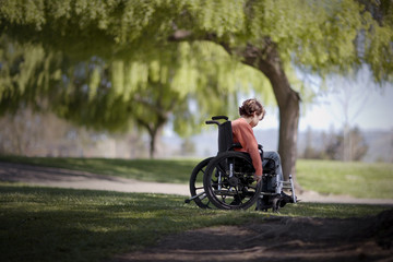 Young boy wheeling himself in a wheelchair at the park.