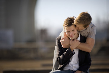 Young man giving his boyfriend a kiss on the ear while standing with his arms around him.