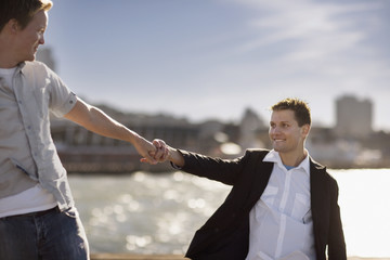 Two young homosexual men looking at each other while holding hands.
