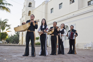 Portrait of five musicians standing in the street holding instruments while dressed in traditional clothing.