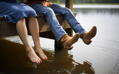 Mature man refuses to take his boots off as he sits next to his barefoot wife on the end of a pier.