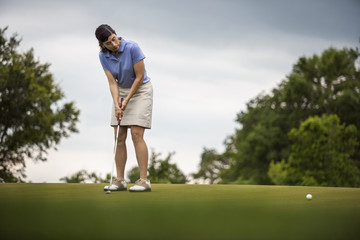 Young woman looks intently at the path of her golf ball after she putted it towards the hole.