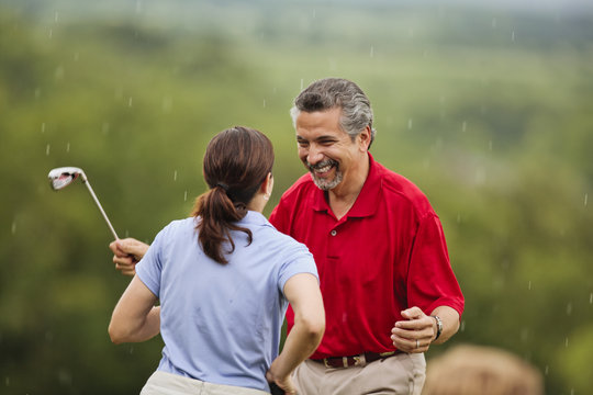 Happy mature couple get caught in sudden rain shower on golf course