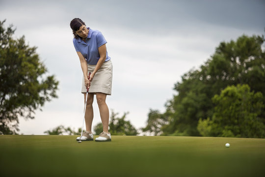 Mature woman looks on as she putts golf ball