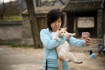 Young adult woman talking a picture of herself and her cat.