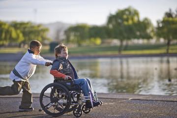 Boy pushing friend in wheelchair through park