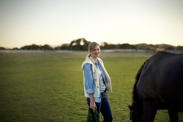 Portrait of a young adult girl standing with a horse in a field.