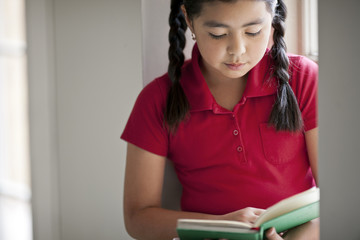 Close up of schoolgirl reading a book