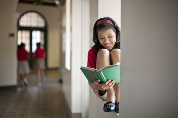Smiling young schoolgirl reading a book.