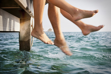 Two pairs of legs dangling off the side of a wooden jetty.