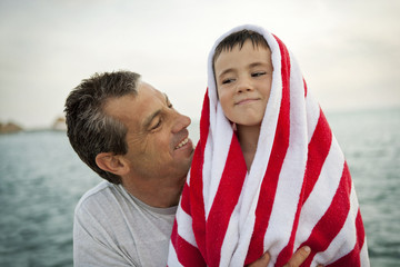 Smiling man looking at his son who is wrapped in a striped towel.