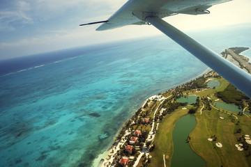Plane flying over a tropical island.