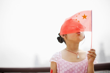 Young girl blowing a small Chinese flag.