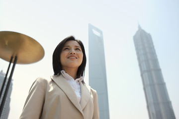 Confident young business woman standing in the city.