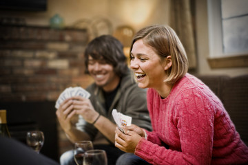 Young woman laughing while holding a hand of playing cards inside a sitting room with friends.