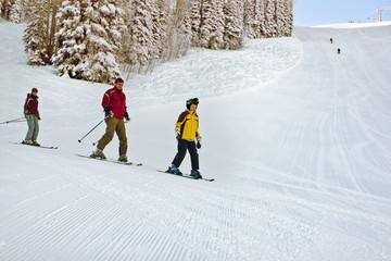 Happy family skiing on slopes.