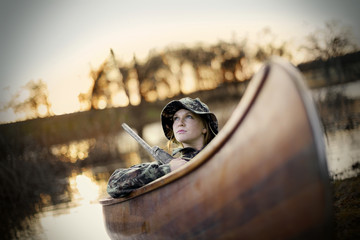 Young adult woman sitting in a canoe with a gun by a lake.