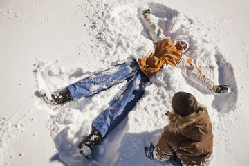 Smiling mid adult woman showing her son how to make a snow angel in the snow.
