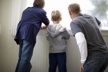 Mid-adult man looking out a window with his two sons.