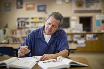 Mature man doing schoolwork at a desk inside a classroom.