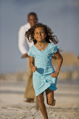 Portrait of a smiling young girl in a blue dress running along a sandy beach followed by her father on a bicycle.