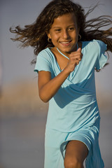 Smiling young girl wearing a blue dress running in the sunshine.