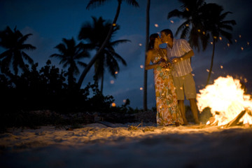 Mid-adult couple standing beside a bonfire on a beach.