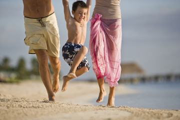 Mother and father swinging their son in the air on the beach
