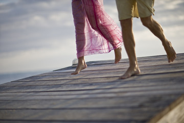 Legs of a couple walking along a pier