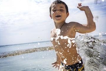 Young boy having fun swimming in the ocean.