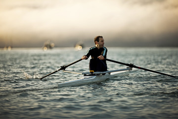Mature man wearing a wetsuit and rowing