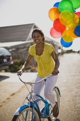 Portrait of a smiling young woman riding a bicycle with balloons tied to it along a suburban street.
