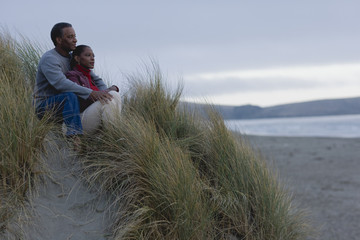 Mid adult couple sitting with arms around each other in tussock grass on a remote beach.