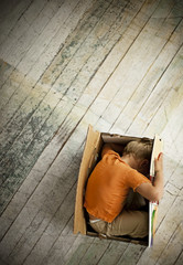Little boy playing in cardboard box