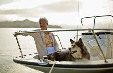 Smiling mature woman relaxes on a boat with her big fluffy dog.