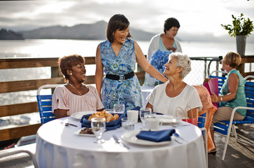 Two mature female friends out to lunch at a seaside restaurant share a laugh with an acquaintance who has come to say hello.