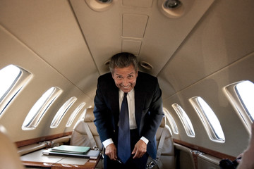 Businessman standing in a private jet and smiling
