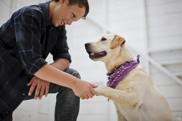 Boy shaking hands with his dog.