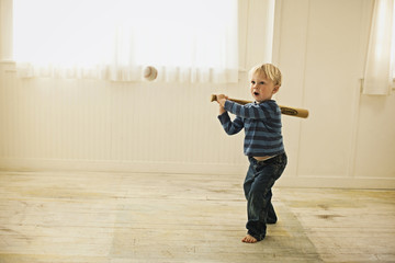 Little boy about to hit baseball with bat