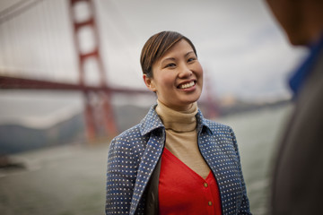 Smiling young woman speaks with a friend by the Golden Gate Bridge in San Francisco, USA.