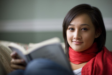 Teenage girl sitting on sofa reading book